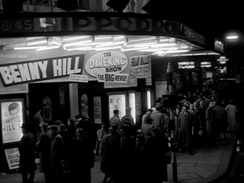 tracking shot along charing cross road and moving past the hippodrome theatre which is advertising a benny hill show. 1956. - ウェストエンド点の映像素材/bロール