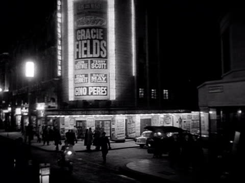 tracking shot along coventry street towards leicester square moving past the neon signs for the prince of wales theatre and then the rialto cinema.... - ウェストエンド点の映像素材/bロール