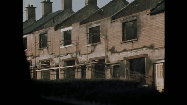 tracking shot along houses, including some destroyed by fire, in the ardoyne district of belfast, northern ireland; 1971. - ruined stock videos & royalty-free footage