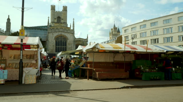 tracking shot along market stalls in cambridge, uk. - cambridge england stock videos and b-roll footage