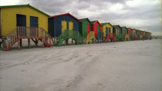 tracking shot along the beach with colourful change rooms and a single deck chair - deck chair stock videos & royalty-free footage