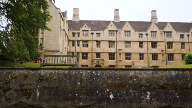 tracking shot along the river cam moving past bodley court at king's college, cambridge. - king's college cambridge stock videos & royalty-free footage