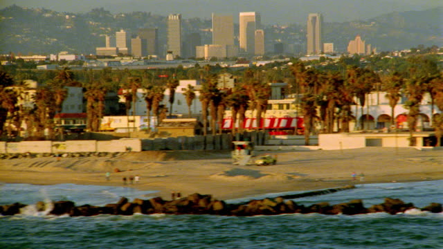aerial tracking shot along venice beach / century city skyscrapers in background / los angeles, california - ビバリーヒルズ点の映像素材/bロール