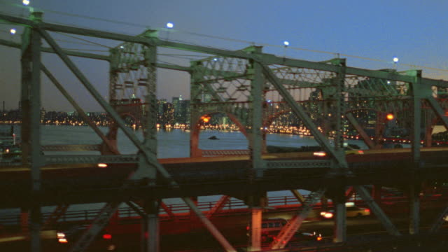 aerial tracking shot alongside 59th street bridge + east river towards manhattan at dusk / nyc - queensboro bridge stock videos & royalty-free footage