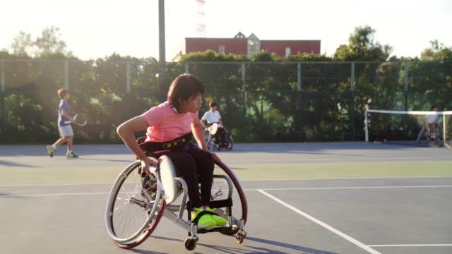 tracking-schuss eine weibliche teenager adaptive tennisspielerin - match sport stock-videos und b-roll-filmmaterial