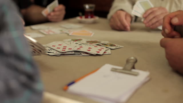 vidéos et rushes de tracking shot around a group of people playing cards at a table. - cartes à jouer