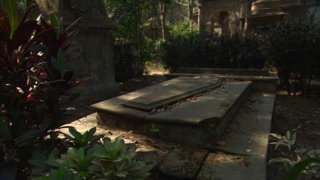 Tracking shot around a stone tomb in Kolkata cemetery.