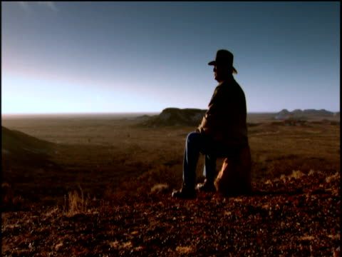 tracking shot around man in stetson sitting on rock and gazing out over landscape partly silhouetted australia - cowboy stock videos & royalty-free footage