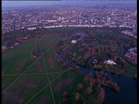 vídeos de stock, filmes e b-roll de tracking shot around regents park with lakes and london buildings in the background - parque regents