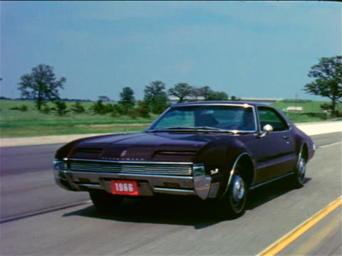 1966 tracking shot black Oldsmobile Toronado driving on country road / industrial