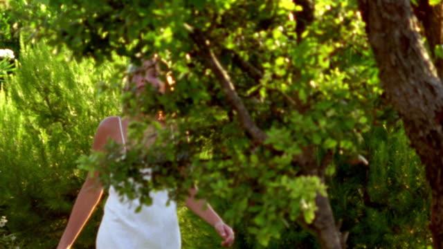 vidéos et rushes de tracking shot blond woman wearing white dress walking past trees - robe blanche