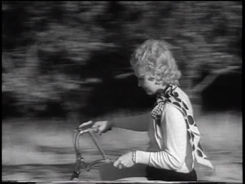 vídeos de stock e filmes b-roll de b/w 1933 tracking shot blonde woman riding on bouncing bicycle on road / san francisco, california / newsreel - 1933
