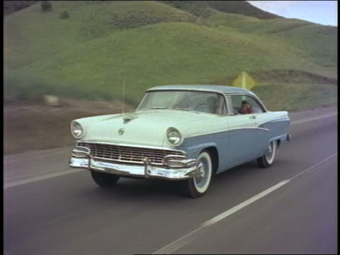 1956 tracking shot blue + white Ford Customline driving on country road past rolling hills