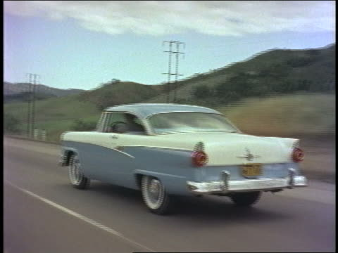 1956 rear view tracking shot blue + white ford customline driving on country road past rolling hills - ford motor company stock videos and b-roll footage