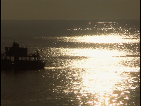 tracking shot boat moving right to left on adriatic at sunset - herumfahren stock-videos und b-roll-filmmaterial