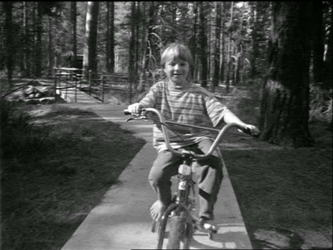 b/w tracking shot boy riding bicycle with training wheels on path in woods towards camera / oregon - di archivio video stock e b–roll