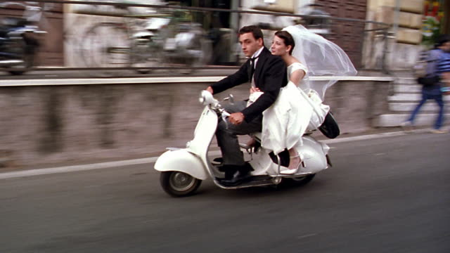tracking shot bride + groom riding scooter on city street / Rome, Italy