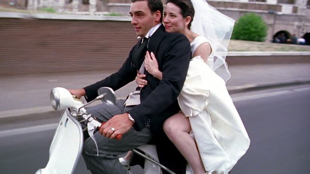 tracking shot bride + groom riding scooter past colosseum / rome, italy - motorino video stock e b–roll