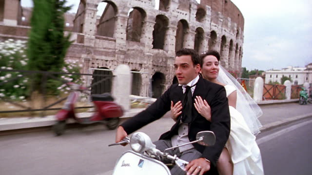 tracking shot bride + groom riding scooter past Colosseum / Rome, Italy