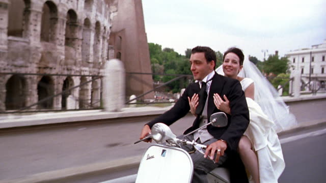 tracking shot bride kissing groom while riding scooter past Colosseum / Rome, Italy