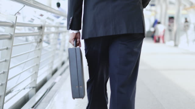 tracking shot: businessman holding briefcase and walking forward. - vista posteriore video stock e b–roll
