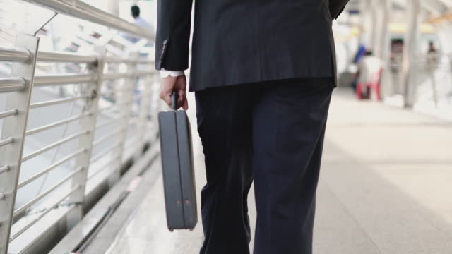 tracking shot: businessman holding briefcase and walking forward. - holding stock videos & royalty-free footage