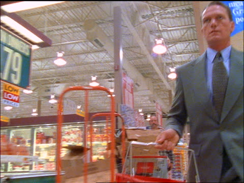 fast tracking shot businessman with shopping basket walking thru supermarket aisles grabbing food - shopping basket stock videos and b-roll footage