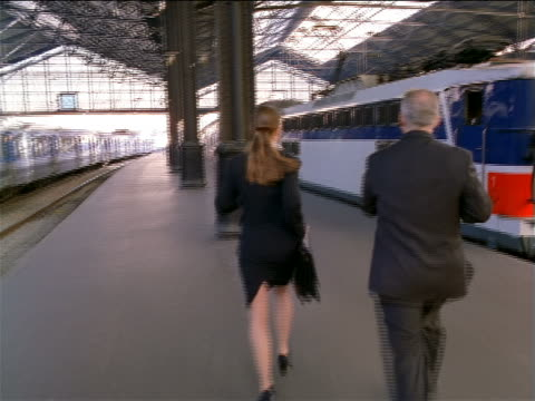 tracking shot PAN businessman + woman chase departing train in Gare de Lyon / man talking on cell phone / Paris