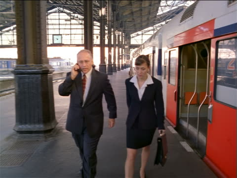 tracking shot PAN businessman + woman exit train, talk + walk in Gare de Lyon / man talks on cell phone/ Paris