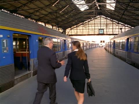 REAR VIEW tracking shot businessman + woman talk + walk in Gare de Lyon / man talks on cell phone / Paris