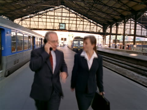 tracking shot businessman + woman talk + walk on platform in Gare de Lyon / man talks on cell phone / Paris