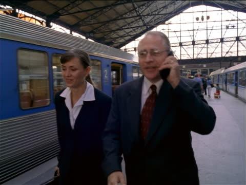 tracking shot businessman + woman talking + walking in Gare de Lyon / man talking on cell phone / Paris