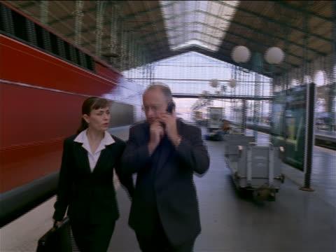 tracking shot pan businessman + woman talking + walking in gare de lyon / man talks on cell phone / paris - tgv点の映像素材/bロール