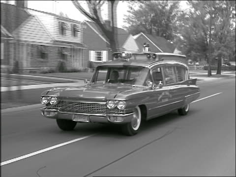 B/W 1961 tracking shot Cadillac ambulance with flashing light driving on suburban street