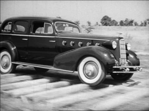 b/w 1934 tracking shot car with whitewall tires driving over logs / industrial - 1934 stock videos & royalty-free footage