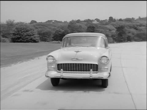 B/W 1955 tracking shot Chevrolet Bel Air Sports Coupe car driving on rural highway towards camera