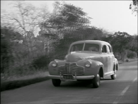 B/W 1941 tracking shot Chevrolet driving on country road