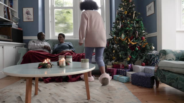 tracking shot, children run and hug parents on christmas morning - slipper stock videos & royalty-free footage