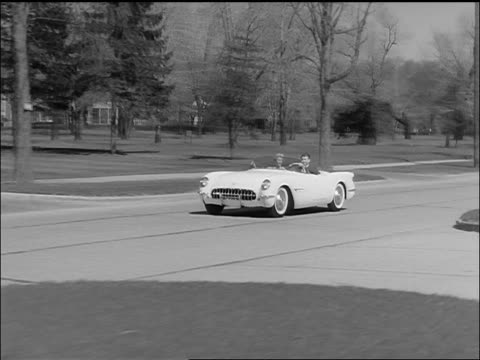 b/w 1953 tracking shot couple driving corvette covertible on street past large houses - chevrolet stock videos & royalty-free footage
