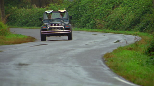 Tracking shot couple driving in Jeep towards CAM on wet curved road w/surfboards on top