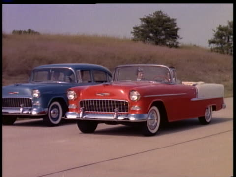 1955 tracking shot couple driving red + white convertible past other cars on country highway