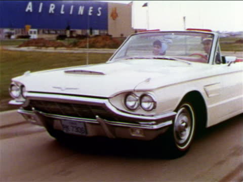 1965 tracking shot pan couple driving white convertible thunderbird past airport / man in pilot's uniform - ford motor company stock videos and b-roll footage