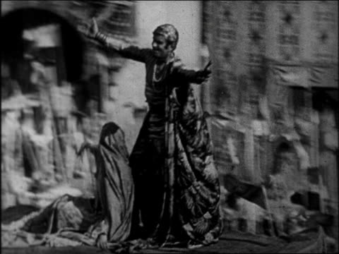 vidéos et rushes de tracking shot couple on magic carpet flying past cheering crowd / feature - 1924