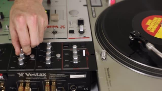vídeos de stock, filmes e b-roll de tracking shot dj mixing two records - misturar