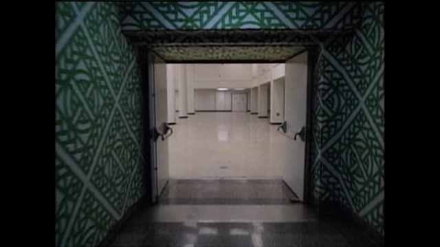 tracking shot down a patterned green corridor to an wide open space with supporting columns inside a secret nuclear bunker beneath a hotel in west... - weapons of mass destruction stock videos & royalty-free footage