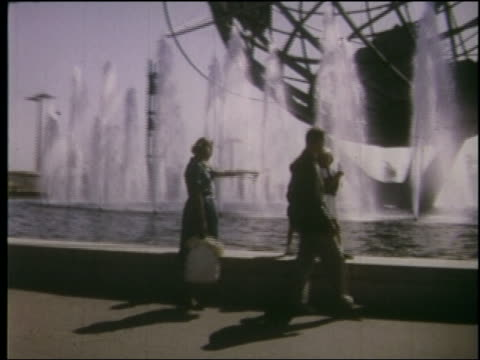 1964 tracking shot family walking on edge of unisphere fountain at ny world's fair - weltausstellung in new york stock-videos und b-roll-filmmaterial