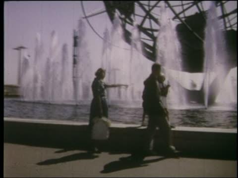 vídeos y material grabado en eventos de stock de 1964 tracking shot family walking on edge of unisphere fountain at ny world's fair - flushing