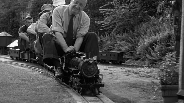 b/w 1951 tracking shot five men riding on mini steam train toward camera - 小さな像点の映像素材/bロール