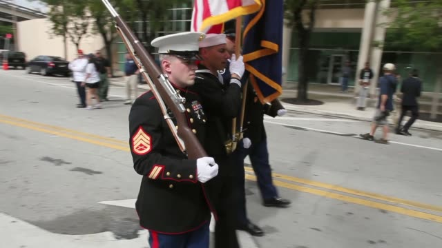 tracking shot flag bearers start the parade to honor veterans of the vietnam war the bay of pigs and all wars the city of miami holds the miamidade... - miami dade county bildbanksvideor och videomaterial från bakom kulisserna