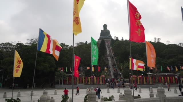 tracking shot, flags by tian tan buddha - tian tan buddha stock videos and b-roll footage